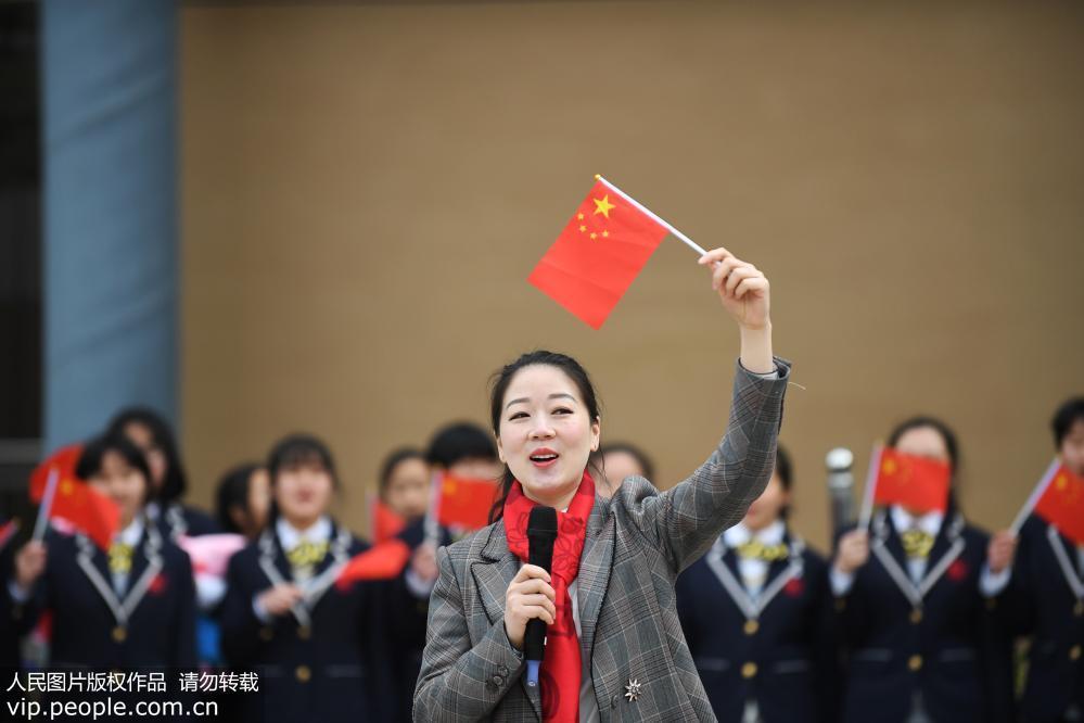 """2019年2月25日,贵州省贵阳市南明区甲秀高中新学期的开学典礼上,全体师生挥动着手中的五星红旗,齐唱《我和我的祖国》,用一场洋溢着青春和爱国热情的歌舞""""快闪"""",迎接新学期的到来。"""
