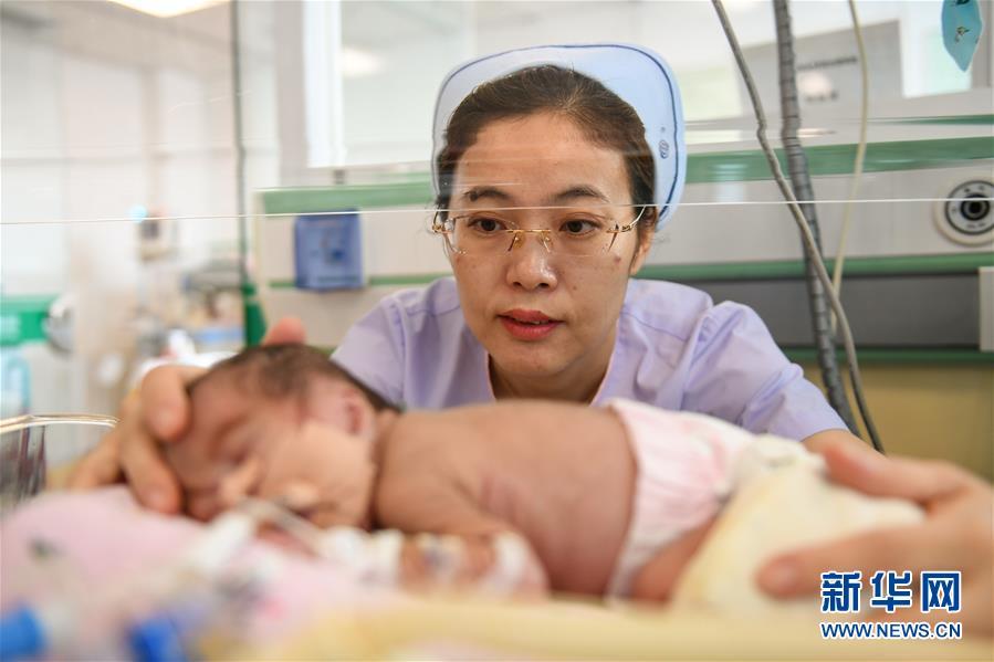 """楊曉玲在保溫箱前護理新生兒(5月9日攝)。今年37歲的楊曉玲是內蒙古自治區人民醫院新生兒科護士長,在科里,她的外號叫""""楊一針"""",只要她拿起針管,再細小的血管都能""""一針到位""""。"""